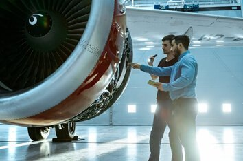 Embedded Software Development Services - Image Of Two Men Discussing A Technical Matter Regarding a Plane Engine